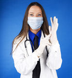 Young pretty woman doctor with stethoscope wearing mask Stock Image