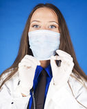Young pretty woman doctor with stethoscope wearing mask Stock Images