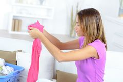 Young pretty woman doing laundry at home Stock Images