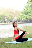 Young pretty woman doing yoga exercises in park Stock Photo