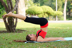 Young pretty woman doing yoga exercises in park Stock Photography