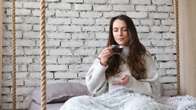 Young pretty woman drinking aroma coffee in bed at home stock video footage