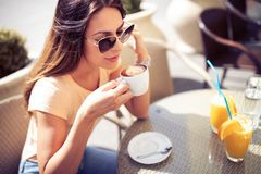 Young pretty woman drinking cappuccino, coffee in cafe outdoors. Enjoying sunny morning in the city stock photo