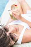 Young pretty woman drinking coconut cocktail Stock Image