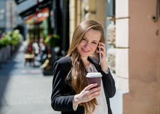 Young pretty woman drinking coffee on the street Royalty Free Stock Photos