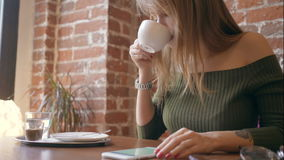 Young pretty woman drinking coffee and using smartphone in cafe. Young girl drinking coffee and using tablet computer in cafe stock video footage