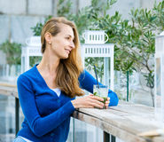 Young pretty woman drinks cocktail Stock Image