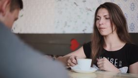 Young pretty woman drinks a cup of coffee as she sits with a man in a cafe. They have fun, laugh and talk stock footage