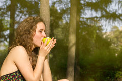 Young pretty woman eating apple on a field stock photography