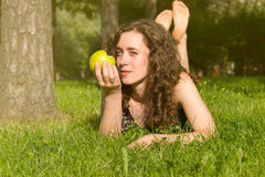 Young pretty woman eating apple on a field Royalty Free Stock Photos