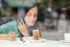 Young pretty woman eating a cake Stock Images