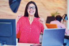 Young pretty woman engineer sitting in the office at desk with laptop and showing thumb up as ok sign Royalty Free Stock Photography