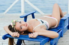 Young pretty woman enjoying sunny day on sun lounge Royalty Free Stock Image