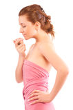 Young pretty woman enjoys a smell of a pink rose Royalty Free Stock Images