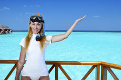 The young pretty woman in equipment for a snorkeling on the sundeck over the sea. Maldives Stock Images