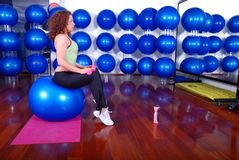 Young pretty woman exercising in a fitness center Royalty Free Stock Photo