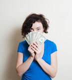 Young pretty woman eyes with face partially covered by dollars Stock Images