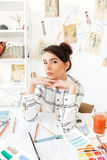 Young pretty woman fashion designer sitting at her work desk Stock Photo
