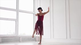 A young lady dances, a woman elegantly performs the movements of modern dance stock footage