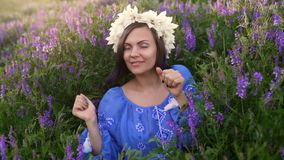 Young pretty woman with flower wreath dancing in purple field. Girl in blue clothing having fun. stock footage