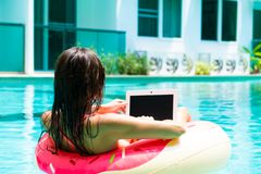 Young pretty woman freelancer is floating on the sea or in the pool in a swimming circle. A girl is relaxing on the royalty free stock images