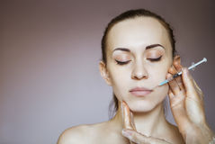Young pretty woman getting cosmetic injection in the face like a Royalty Free Stock Image