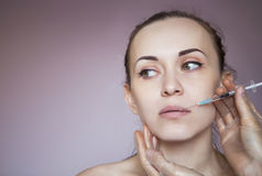 Young pretty woman getting cosmetic injection in the face Royalty Free Stock Images