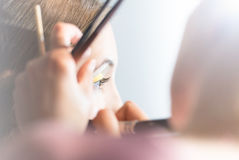 Young pretty woman getting make-up with brush. Stock Photo