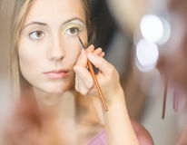 Young pretty woman getting make-up with brush. Stock Image