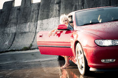 Young pretty woman getting out of sport car. Portrait of sexy blonde young pretty woman getting out of red sport tuning car. Car has wet body after rain, there Royalty Free Stock Photos