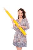Young pretty woman with giant yellow pencil Royalty Free Stock Photo
