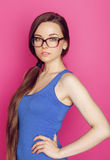 Young pretty woman in glasses smiling on pink Royalty Free Stock Photos