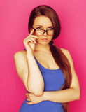Young pretty woman in glasses smiling on pink background Stock Images