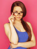 Young pretty woman in glasses smiling on pink background Royalty Free Stock Photo