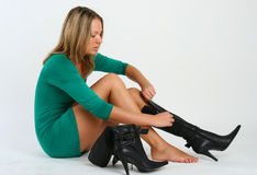 Young pretty woman in green dress putting on boots. Studio shot Stock Photography