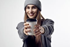 Young pretty woman in a grey clothes holds a coffee paper cup. Take away package for layout. Focus on cup. Stock Images