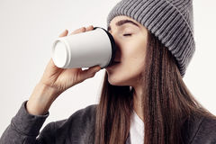 Young pretty woman in a grey hat drink a coffee from paper cup. Eyes closed. Takeaway package for layout. Stock Photos