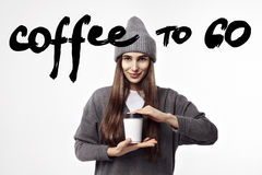 Young pretty woman in a grey outfit drinking a coffee from paper cup. Takeaway package design layout. Stock Images