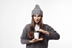 Young pretty woman in a grey outfit drinking a coffee from paper cup. Takeaway package design layout. Stock Photos