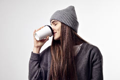 Young pretty woman in a grey outfit drinking a coffee from paper cup. Takeaway package design layout. Royalty Free Stock Photos