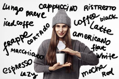 Young pretty woman in a grey outfit drinking a coffee from paper cup. Takeaway package design layout. Stock Photography