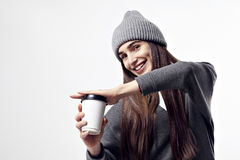 Young pretty woman in a grey outfit with a paper cup of coffee. Take away package for layout. Royalty Free Stock Images
