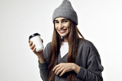 Young pretty woman in a grey outfit with a paper cup of coffee. Take away package for layout. Royalty Free Stock Image