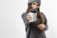 Young pretty woman in a grey outfit show a coffee from paper cup. Takeaway package for layout. Focus on cup. Royalty Free Stock Images
