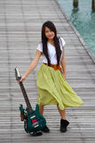 Young pretty woman with guitar on bridge Royalty Free Stock Photos