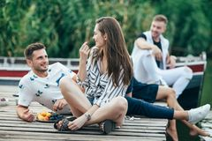 Young pretty woman and handsome man flirting while relax on picnic near river royalty free stock image