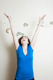 Young pretty woman happy with dollars falling on her head Stock Image