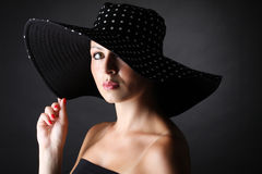 Young and pretty woman with hat on black background royalty free stock photography