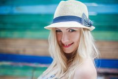Young smiling woman in a hat with blondie hairs. Young pretty woman in a hat with blondie hairs on the background of colorful wall. Smiling face Royalty Free Stock Photos