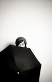 Young pretty woman with hat, eyes from behind black umbrella Royalty Free Stock Image